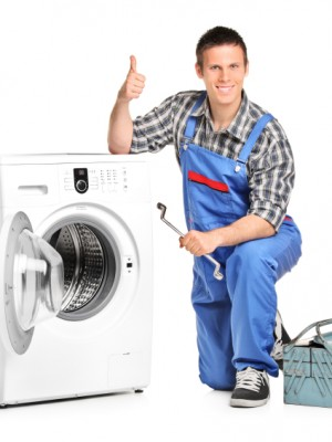 Repairman giving thumb up next to a washing machine